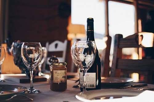 glass closeup photo of two empty wine glasses beside wine bottle wine