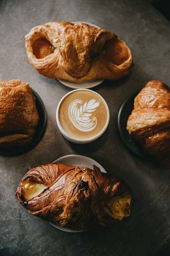 croissant coffee surrounded by four baked breads bread