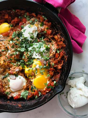 bowl cooked meat with eggs in skillet shakshuka