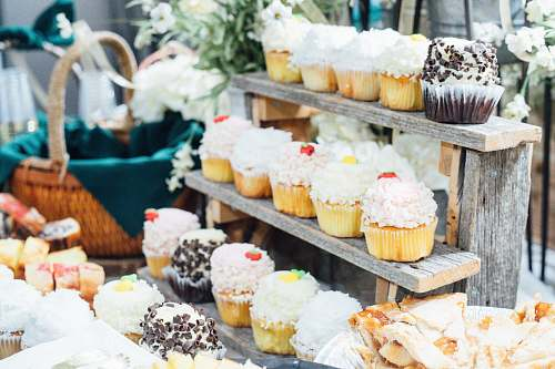 creme cupcakes on wooden stand beside basket cream