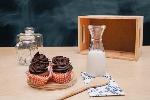 cake four cupcakes on brown coaster and milk jar cupcake