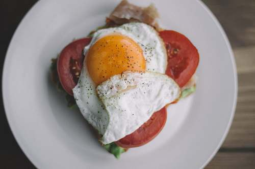 cream fried egg with black pepper and sliced tomatoes egg