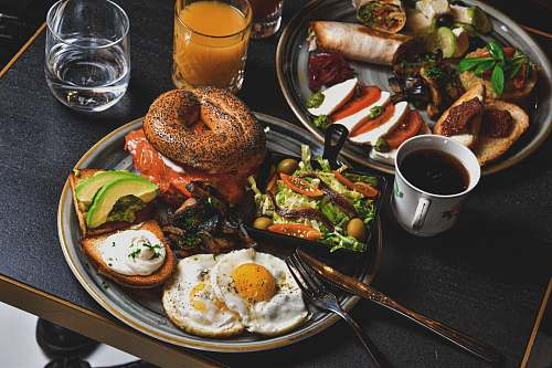 bread hamburger, fried eggs, avocado slices, and bread on round gray plate burger