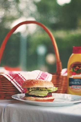 burger hamburger on ceramic plate beside picnic basket meal