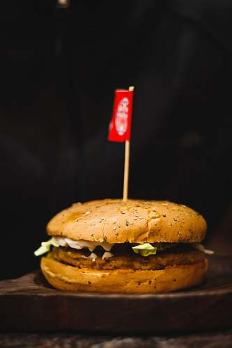 bread hamburger on wooden surface with small flag burger