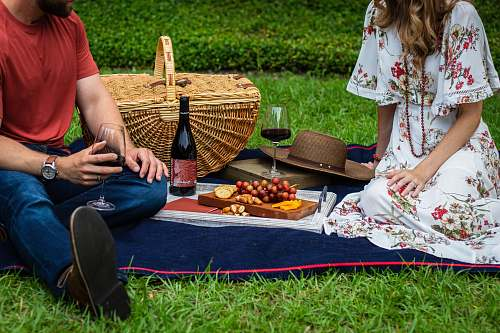 meal man and woman sitting on blue textile beside brown wicker picnic basket vacation