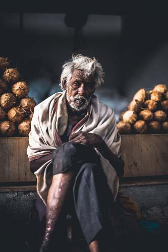 vegetable man sitting beside coconut stand plant