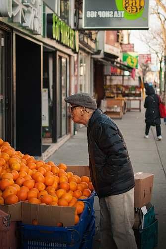 fruit man standing beside orange fruits display plant