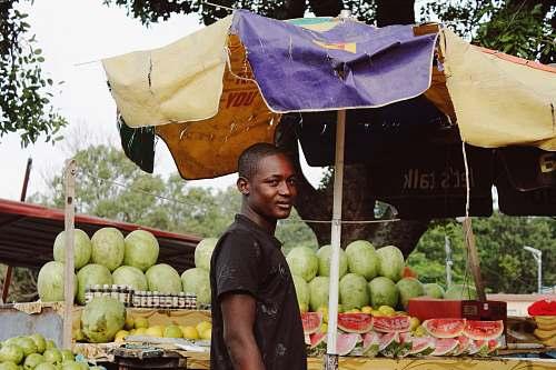 fruit man standing near watermelon fruit stand melon
