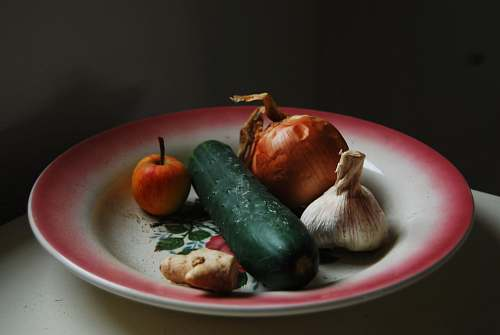 garlic onion, garlic, ginger, and green vegetable on round white and red plate vegetable