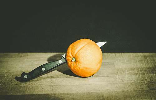 fruit orange fruit and gray and black knife on brown wooden board low-light photography orange