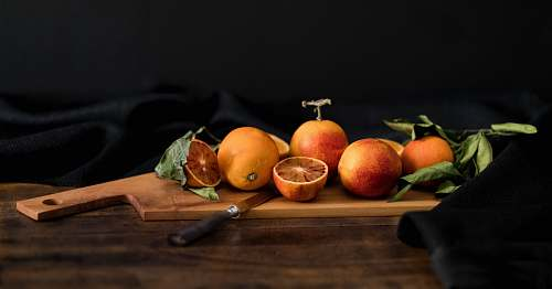 orange orange fruits on brown wooden chopping board with knife fruit