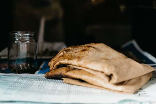 bread pair of brown leather gloves beside glass jar on newspaper pita