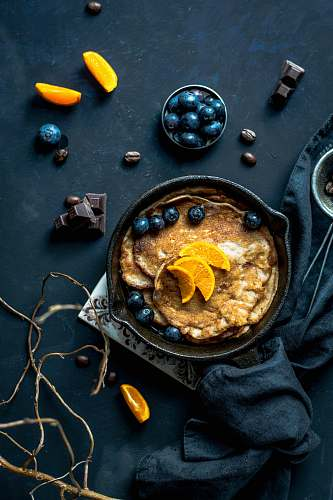 food photography pancake with orange and blueberries beside scattered chocolate and coffee beans food styling