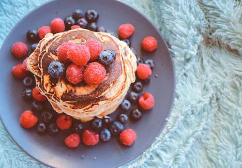 pancake pancakes with blueberries and raspberries on gray plate stack