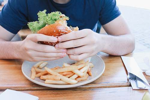 human person eating hamburger with fries on plate fries
