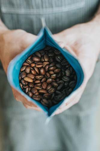 coffee person holding coffee beans in pack plant