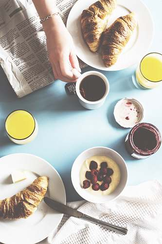 breakfast person holding white ceramic mug on table croissant