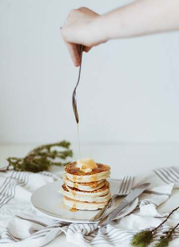 bread person pouring honey on top of pancake pancake