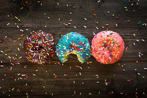 paper pink, blue, and chocolate with sprinkles doughnuts on table confetti