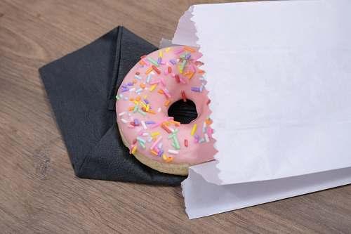 dessert pink donut on white paper bag pastry
