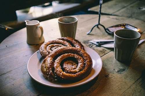cup plate of glazed bread near mugs on tabletop breakfast