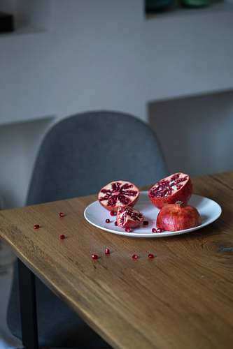 plant pomegranate fruit sliced into half on white plate produce