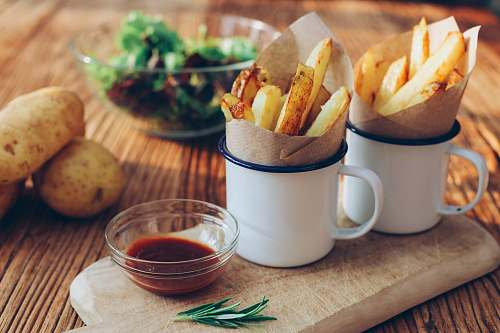 fries potato fries on mugs beside sauce cup