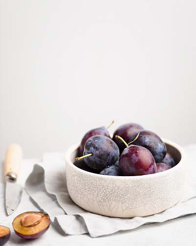 produce purple grapes on round white bowl plum