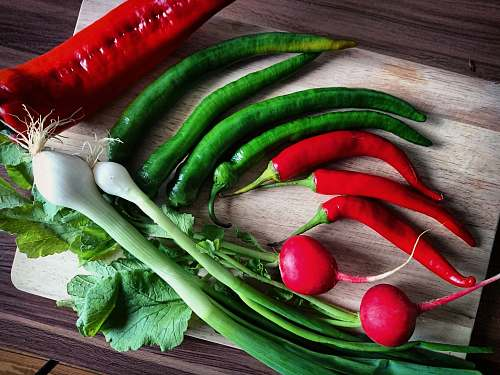 vegetable red and green chilis and red bell pepper on brown chopping board radish
