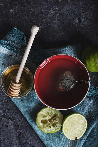 tea red ceramic bowl filled with water beside lime and honey drink