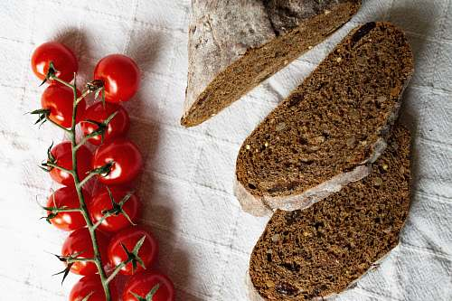photo bread red cherry tomatoes beside sliced bread on white textile plant free for commercial use images