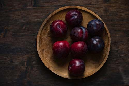 fruit red plum fruits on round brown wooden plate plum