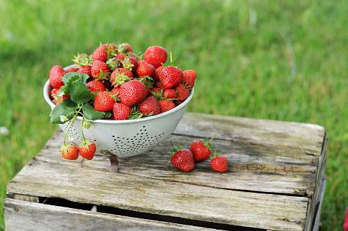 plant red strawberries on wooden surface and in colandar fruit