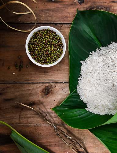 plant rice in green leaf beside bowl of seeds vegetable
