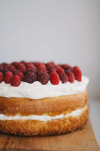 confectionery round cake with white frosting topped with red raspberries sweets