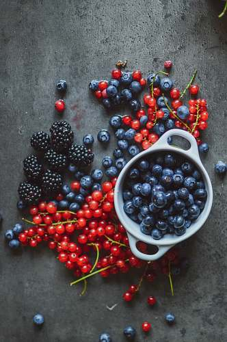 fruit round red and blue berries beside bowl blueberry