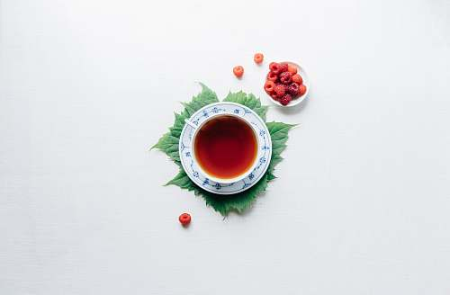 tea round white cup with saucer filled with red liquid drink