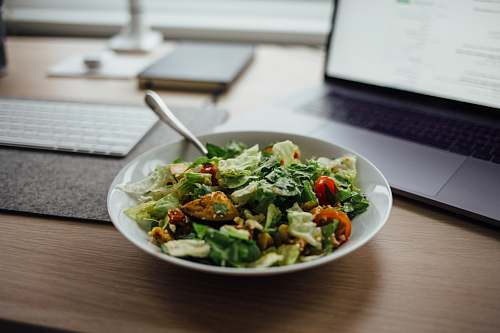 salad salad on white ceramic bowl on top of table near laptop meal