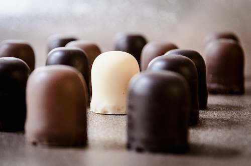 confectionery selective focus photo of milk chocolate surrounded by chocolate sweets