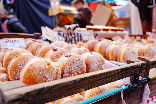 person selective focus photography of doughnuts display on brown wooden trays near person wearing black hoodie donut