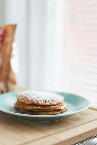 pancake selective focus photography of four piece pancakes with powdered sugar on top in blue ceramic plate bread