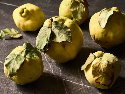produce several round green citrus fruits quince