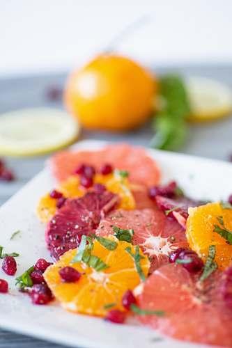 plant shallow focus photo of sliced fruits on white ceramic tray citrus fruit