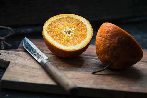 fruit shallow focus photography of sliced lemon beside knife orange
