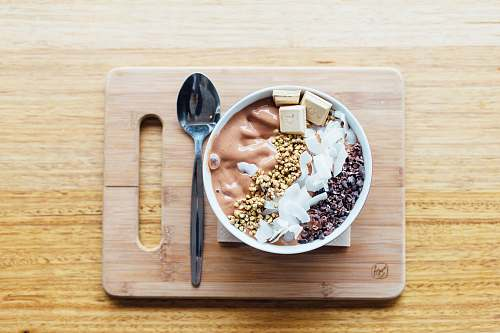 spoon silver spoon and white bowl on brown wooden chopping board breakfast