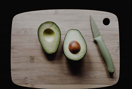 fruit sliced avocados on top of brown wooden chopping board in top view photography avocado