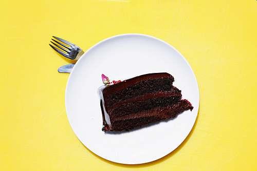 yellow sliced cake on white ceramic saucer fork