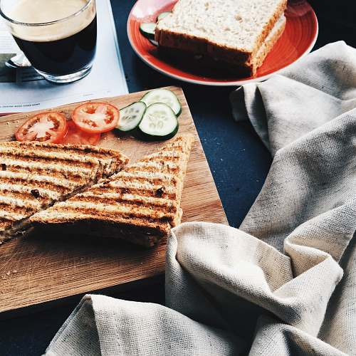 breakfast sliced grilled bread beside tomatoes and cucumbers on brown wooden board drink