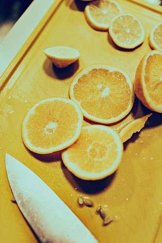 fruit sliced lemon near gray stainless steel knife citrus fruit